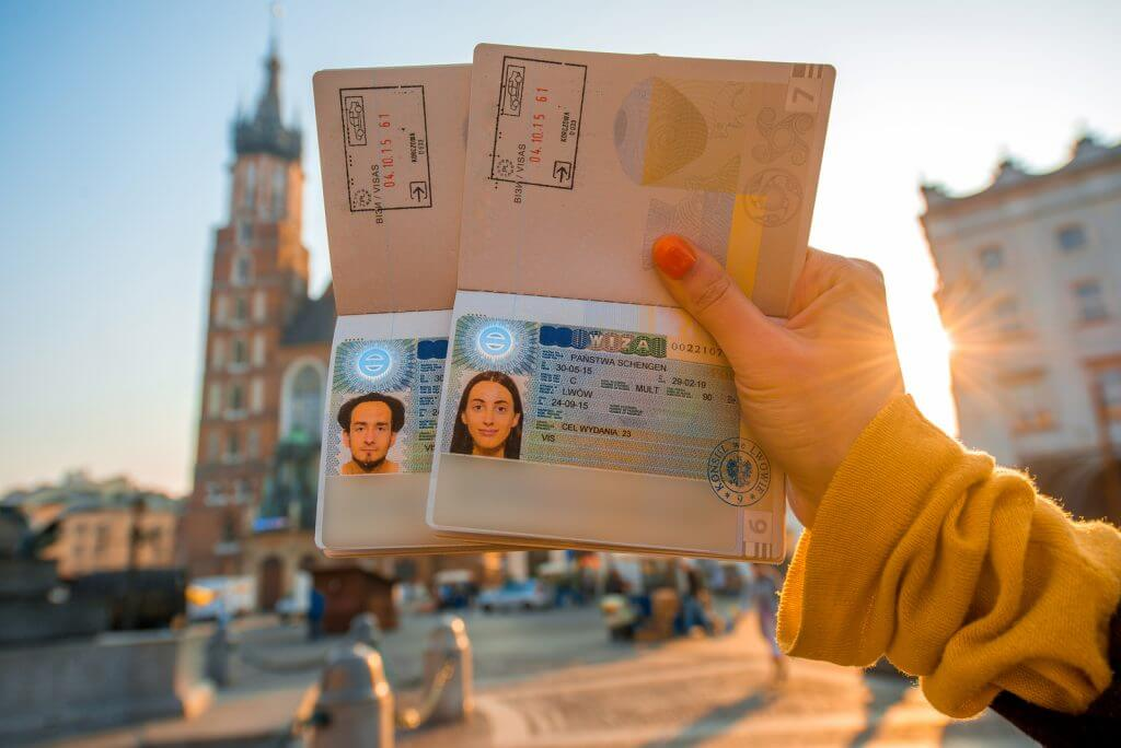 Female hands holding Ukrainian passports with Shengen visas on the Krakow city