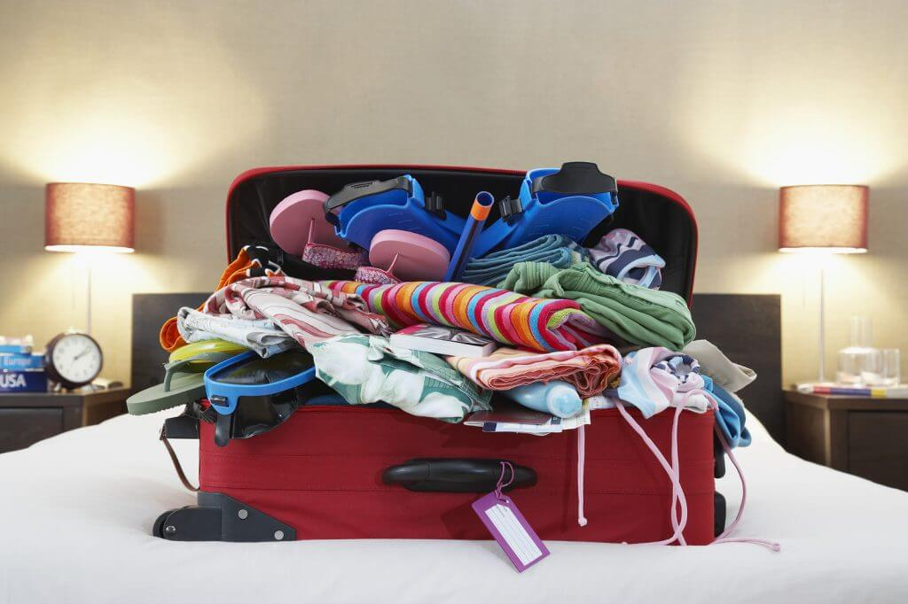 overpacked suitcase on bed
