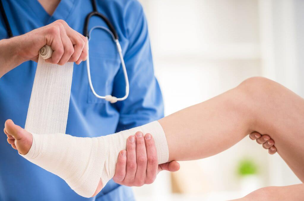 f male doctor bandaging foot of female patient at doctor's office.