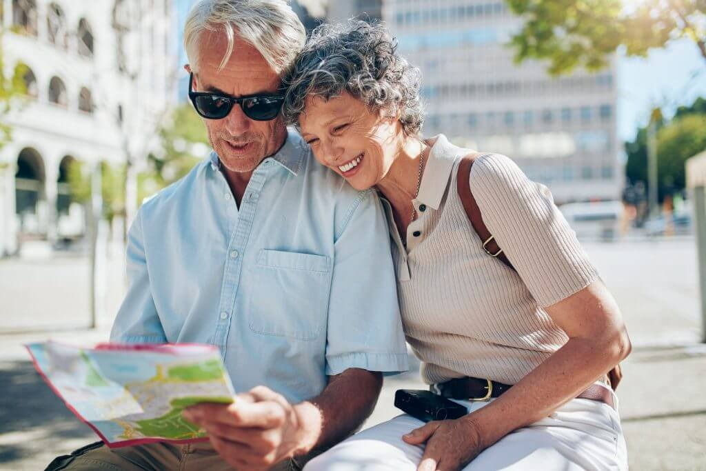 Happy mature couple looking at a city map.