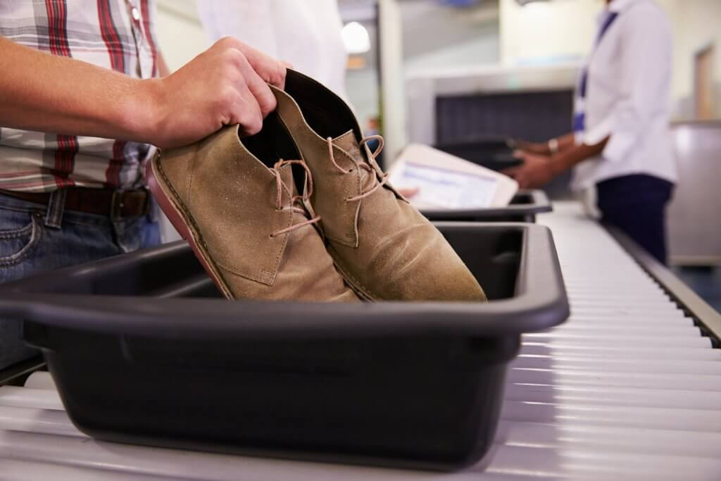 Man putting shoes into TSA security tray at airport