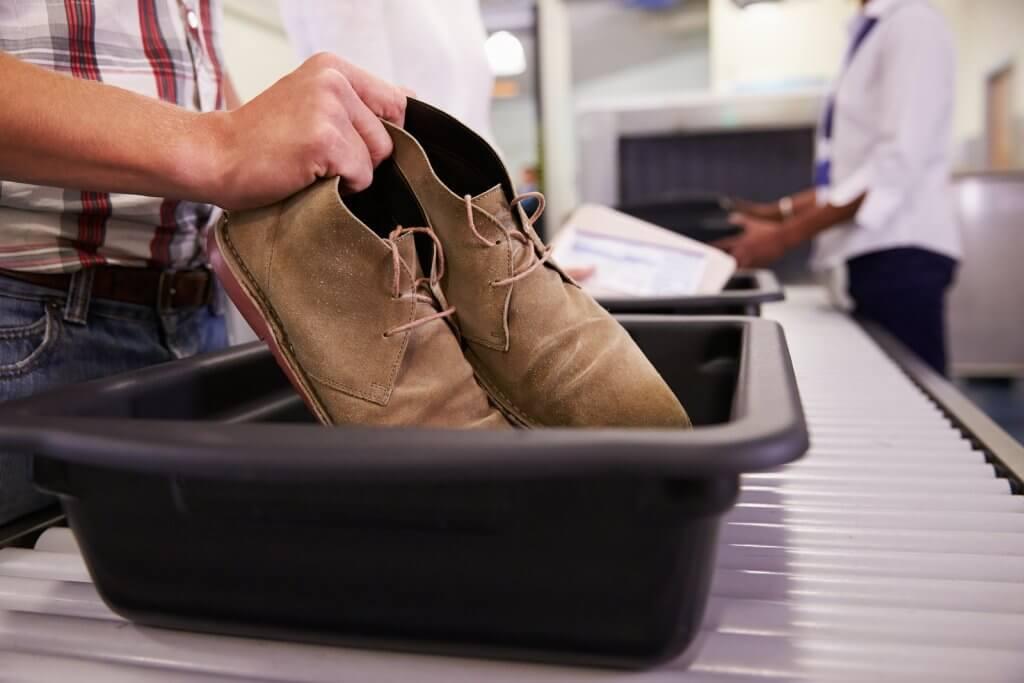 Man putting shoes into TSA security tray at airport