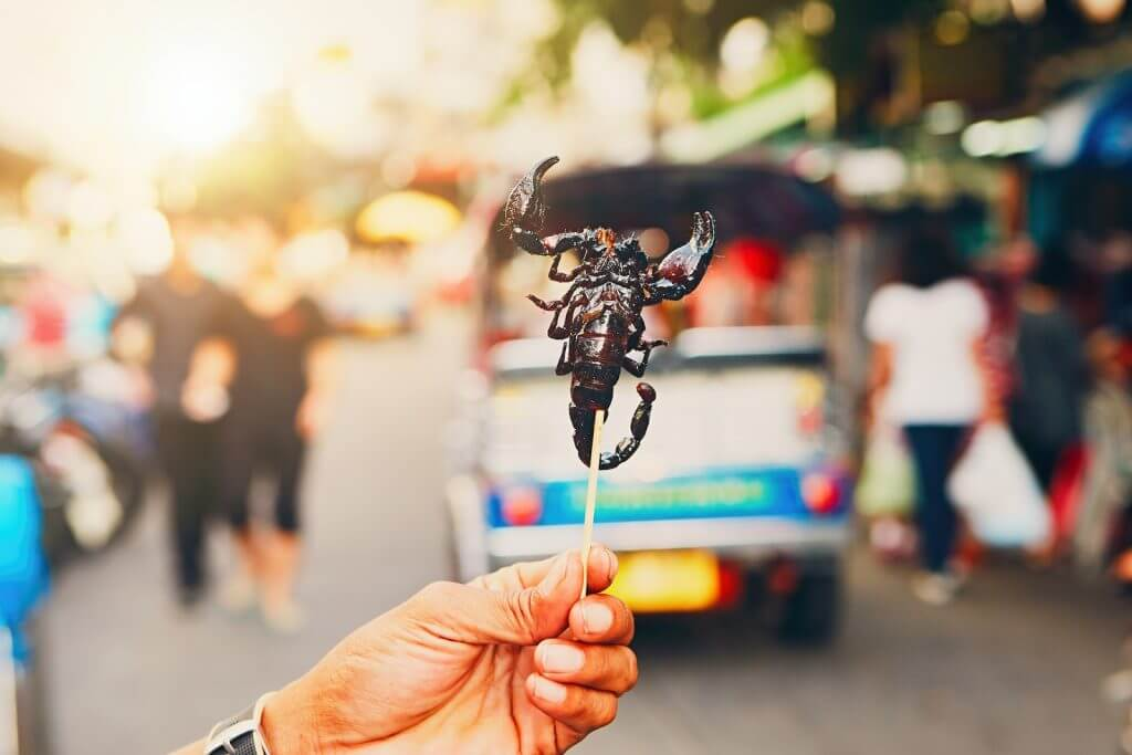 Hand of the Thai vendor showing roasted scorpio. Street market in central Bangkok Thailand.