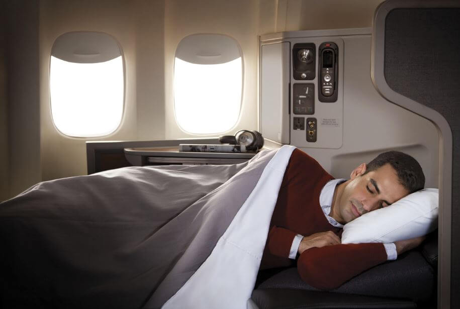 Man sleeping on lie-flat bed in business class flight.