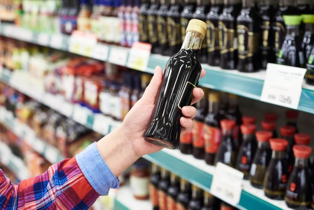 Buyer with the soy sauce in a store