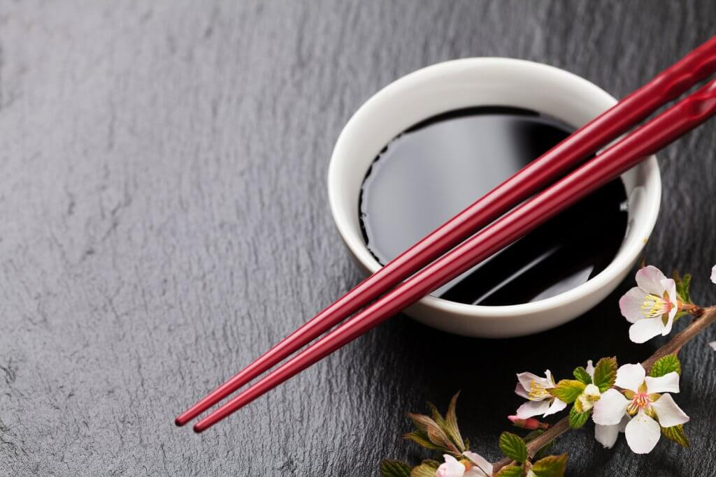 Japanese sushi chopsticks, soy sauce bowl and sakura blossom on black stone background.
